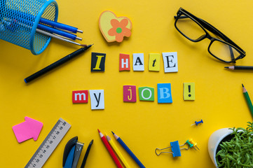 Workplace with I Hate My Job sign of carved letters and office supplies on yellow background