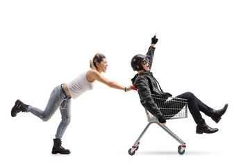 Punk girl pushing a shopping cart with a biker riding inside and pointing up