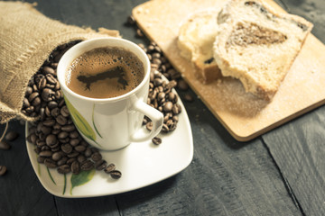 Cup of coffee and pound cake - Hot cup of coffee on its plate, surrounded by coffee beans coming out from a small burlap sack and slices of pound cake in background