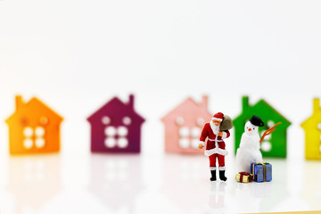 Miniature people: Santa Claus and snowman  with gift standing before Wooden house model. Merry Christmas and Happy New Year concept.