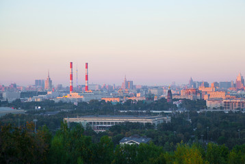 the skyline of a large city at sunset. Residential houses, industrial pipe