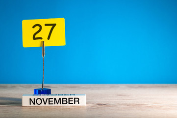November 27th. Day 27 of november month, calendar on workplace with blue background. Autumn time. Empty space for text