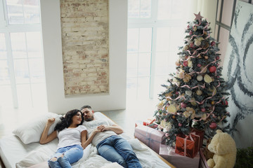 Happy couple of lovers lie on the bed. Christmas interior. Lovers together