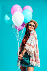 Hippie girl holding colored balloons