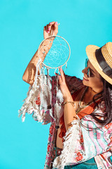 hippie girl looking at dreamcatcher