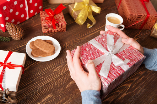 4c98c3a679 Man holding Christmas presents laid on a wooden table background ...
