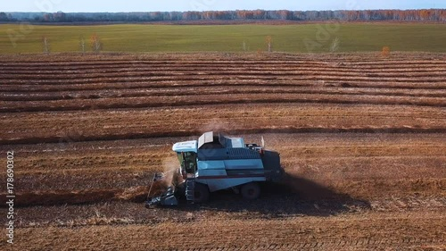aerial footage of a modern tractor plowing dry field, preparing land for sowing. seeding at the end of the season. Plant new grains for the next year