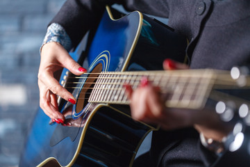 closeup of hands of a musician playing acoustic guitar