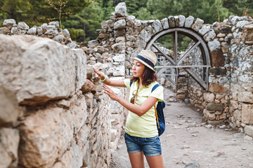 Young female tourist with blue backpack exploring ancient greek town Olympos, near Cirali village in Turkey