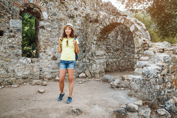 Happy woman tourist travels in famous ancient town Olympos in Turkey, historical and archeology concept