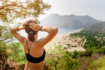 woman tourist enjoy the view of the Mediterranean sea over mountain top, Cirali, Turkey