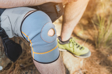 close up of knee support brace on leg of a traveler man during hiking outdoors in nature