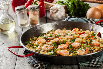 Traditional seafood paella with shrimp, fish and chicken seved in paellera