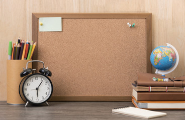 blank cork board with alarm clock, book on wooden desk.
