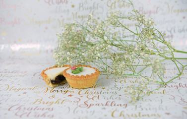 christmas food photography image with mince pies holly and white green xmas flowers on christmas words wrapping paper