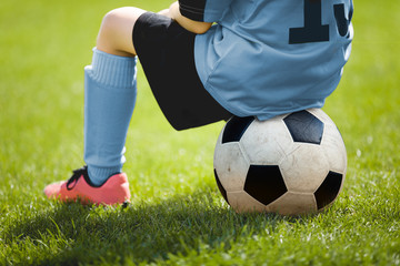 Child Sitting on Soccer Ball. Young Boy with Soccer Ball on the Pitch. Soccer Grass in the Background. Younth Sport Football Background