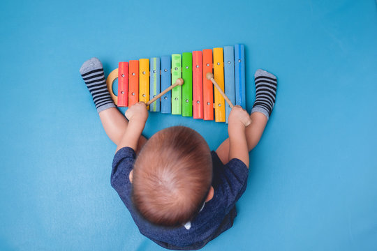 Bird eye view of Cute little Asian 18 months / 1 year old baby boy child hold sticks & plays a musical instrument colorful wooden toy xylophone