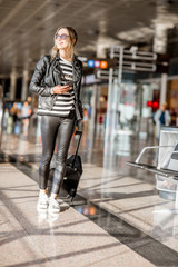 Young business woman dressed casually walking with suitcase at the departure hall of the airport waiting for the flight