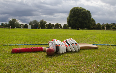 Cricket bat and gloves on the boundary line waiting to be used in English village game.