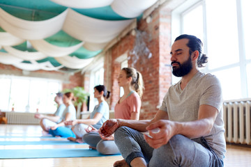 man with group of people meditating at yoga studio