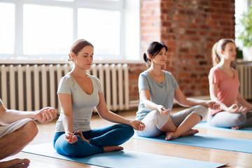 group of women making yoga exercises at studio