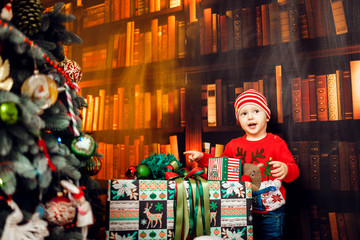 Funny little boy plays with present boxes before a Christmas tree