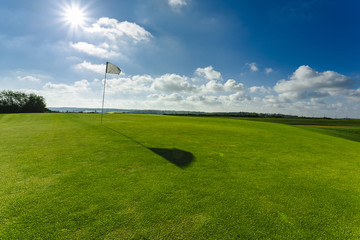 View of a green golf course, hole and flag on a bright sunny day. Sport, relax, recreation and leisure concept. Summer landscape with sunbeams