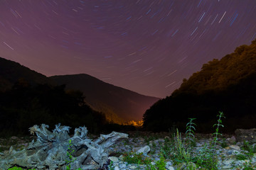 Long exposure photo of night landscape of ravine, mountains and star trails, Sochi, Russia