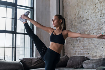 Sporty Caucasian girl doing standing split exercise in her apartment with loft interior
