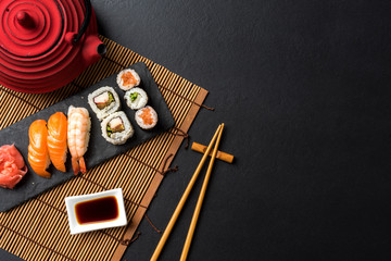 Set of sushi with wasabi, soy sauce and teapot on black stone background. Top view