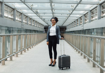 Smiling woman standing with suitcase in a center of corridor in transportation terminal