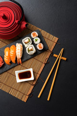Foto op Aluminium Sushi bar Set of sushi with wasabi, soy sauce and teapot on black stone background. Top view