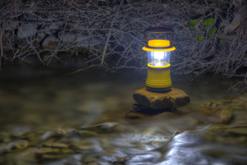 Luminous hand lantern standing on the stone which lying in flowing water of river