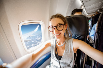 Young happy woman making selfie photo sitting on the aircraft seat near the window during the flight in the airplane