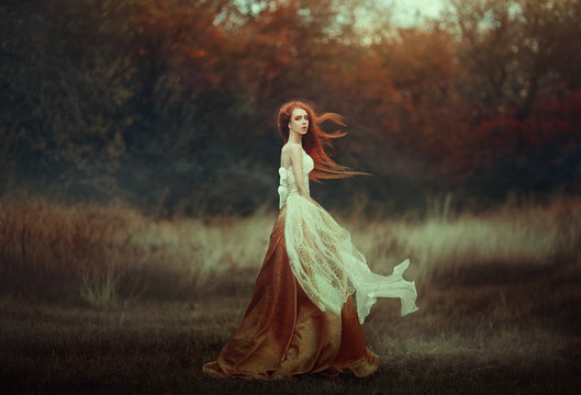 Beautiful young woman with very long red hair in a golden medieval dress walking through the autumn forest. Long red hair develops in the wind.