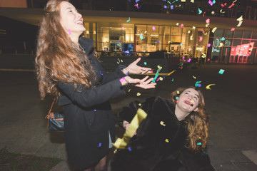 two young women outdoor city night playing with confetti - celebrating, party, having fun concept