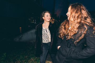 two young women friends walking outdoor night having fun - happiness, girl power, interaction concept