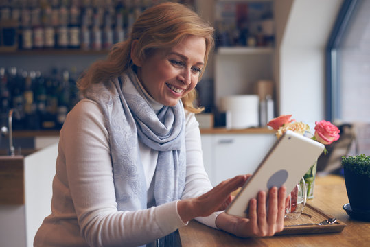 Smiley mature woman using digital tablet in cafe