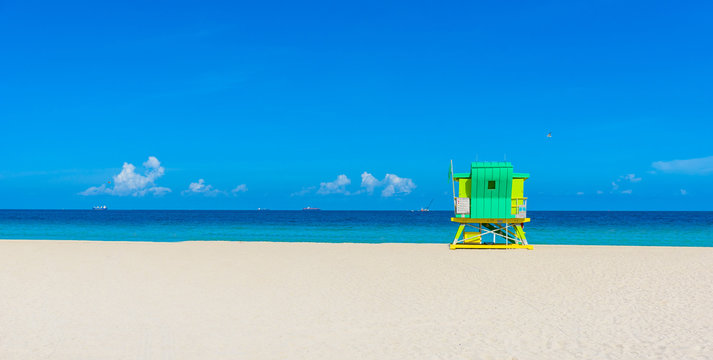 Miami South Beach, lifeguard house in a colorful Art Deco style at sunny summer day with the Caribbean sea in background, world famous travel location in Florida, USA