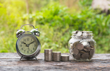 Coins in jar with money stack step growing money and alarm clock, Concept finance business and saving investment.