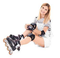 Attractive woman with roller skates against white background