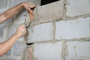 Migrant worker building cinder block wall in desert setting.
