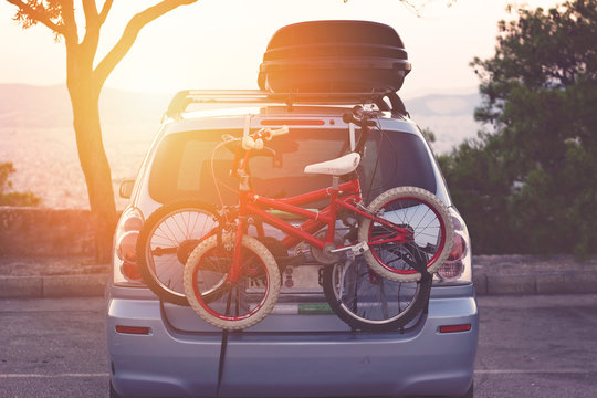 Family car with small kids bicycles rack, ready for travel, making a break on parking