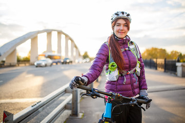 Photo of sportive woman in helmet on bicycle on bridge in city