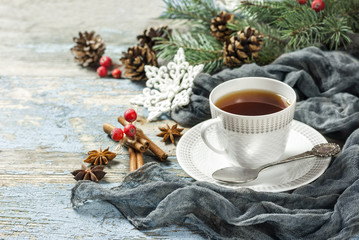 Cup of tea with spices and Christmas decoration on wooden blackboard