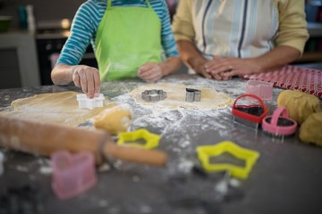 Grandmother and granddaughter cutting dough with a cookie cutter