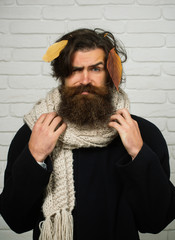 Man hipster at autumn leaves in scarf.