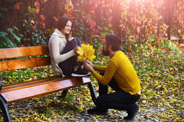 Couple in love in autumn park at bench.