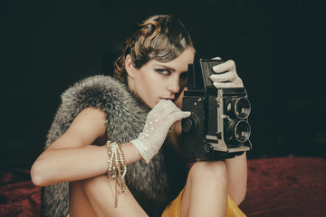 Woman with retro hair, makeup and old camera.