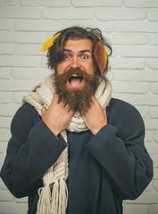 Guy with long beard at brick wall in fall.